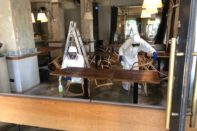 people in hazmat suits wiping down a table in an empty restaurant