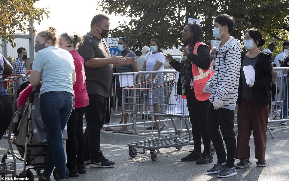 People could be seen wearing masks as they queued behind barriers outside the Chingford Costco in north London