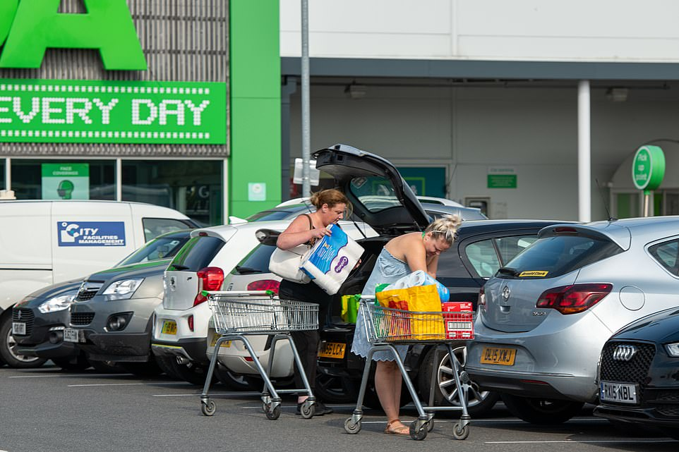 Customers place their items into their car after shopping at an Asda supermarket in Middleton, Leeds, amid the coronavirus pandemic