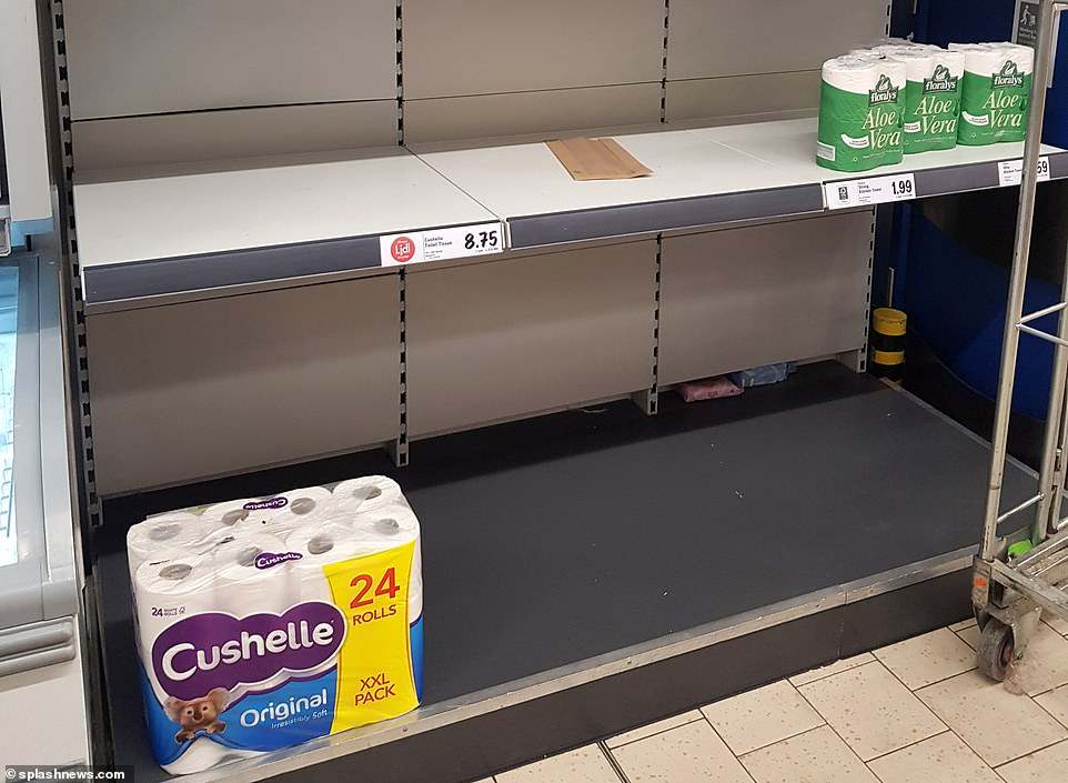 Members of the public panic buy toilet roll at a supermarket in Camden Town, north London, as the country gears up for a series of tougher restrictions amid the coronavirus pandemic